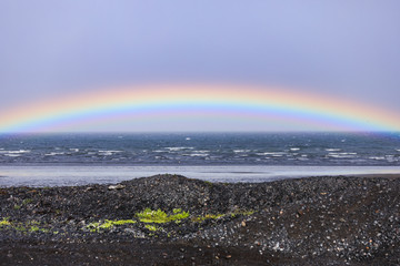 Rainbow over the atlantic ocean in iceland