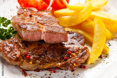 Foto op Canvas Steakhouse Grilled steaks, French fries and vegetables