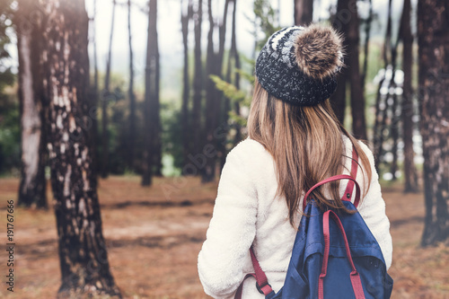 Young woman traveler walking in the forest