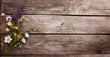 Wild flowers on old grunge wooden background (chamomile lupine dandelions thyme mint bells rape)