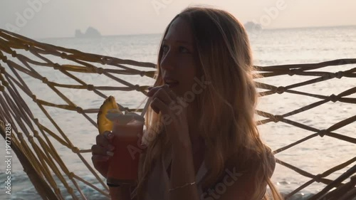 Young Woman Drink Cocktail Swinging in Hammock at Sunset