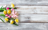 Yellow daffodils and pink tulips with gift box on white weathered wooden boards - 191777461