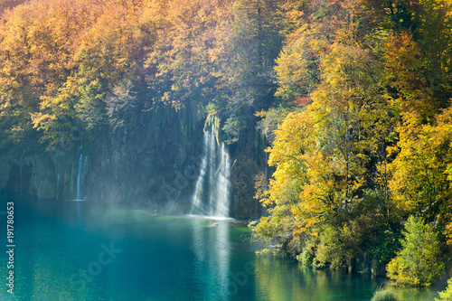 An amazing display of autumn in Plitvice Lakes National Park. The great variance of changing colors of the trees and two waterfalls falling into the turquoise colored lake water.