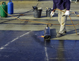 Worker preparing part of bitumen roofing felt roll for melting by gas heater torch flame - 191783262