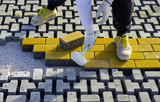 Construction worker laying interlocking paving concrete onto sheet nonwoven bedding sand and fitting them into place. - 191783292