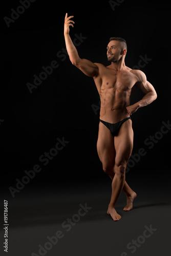 Plexiglas Fitness Handsome muscular athlete view in dark room