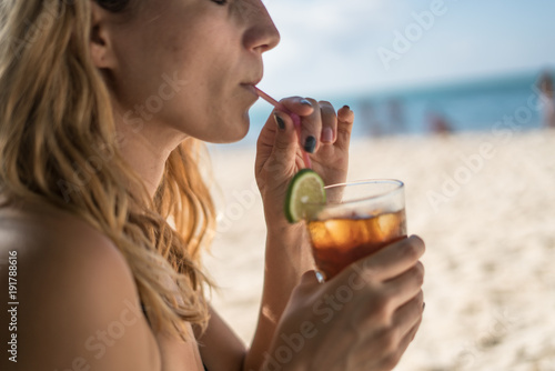 beautiful young woman mixing her cocktail with a plastic straw in a glass, decorated with a lime slice, on the beach on a hot warm summer day in the Caribbean sea