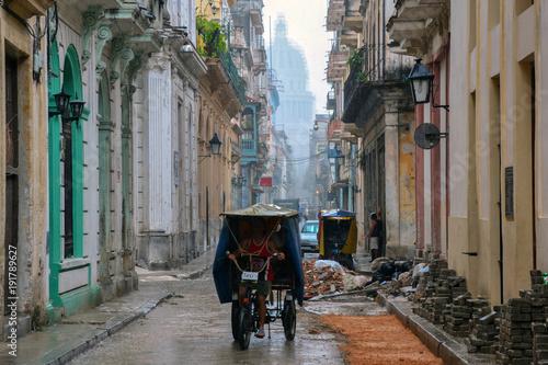 Fotobehang Smalle straatjes Taxista trabajando bajo la lluvia de La Habana
