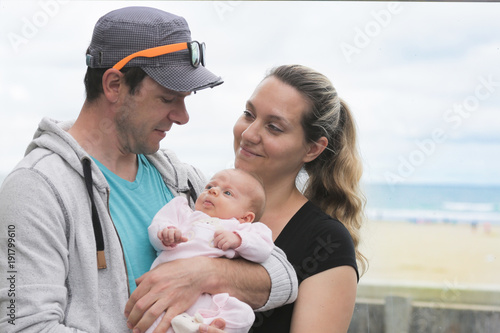 Close-up Portrait of Young Beautiful Mother and FatherHolding Her Newborn Baby Girl at Hot Summer Day, Sea Side, Pacific Ocean Beach, Family Vacation, Happy Motherhood Concept, Happy Family Concept