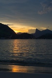 Dusk on the beach of San Francisco, Niteroi, Rio de Janeiro, Brazil. The sky is orange, the sea calm with the sun reflecting in the sea; you can see the silhouette of the mountains of the city of Rio. - 191801891