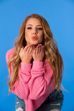 Beautiful young woman in pink sweater over vibrant blue background