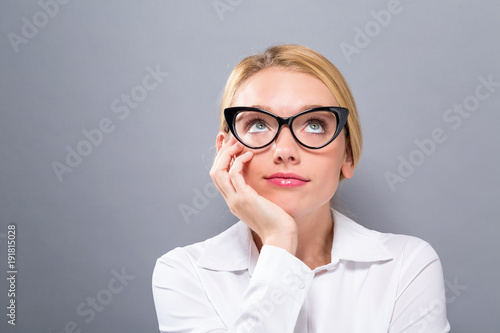 Young businesswoman in a thoughtful pose on a solid background