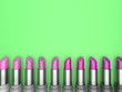 Leinwandbild Motiv 3d illustration set of lipstick with rose-colored hues on a green background.