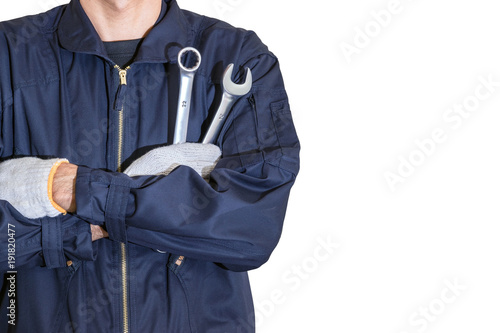 Car repairman wearing a dark blue uniform standing and holding a wrench that is an essential tool for a mechanic isolated on white background.