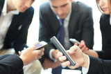 Group of people using smart phones sitting at the meeting, close up on hands. - 191828404