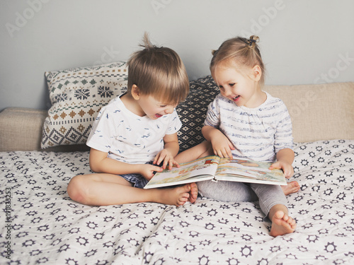 Foto Murales Two kids sitting on bed and reading a book