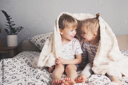 Leinwanddruck Bild Two pretty kids embrace under blanket