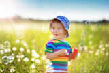 Baby boy standing in grass on the fieald with dandelions - 191834621