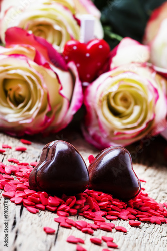 Sweet chocolate hearts, Valentines day composition with red roses, vintage wooden background, selective focus