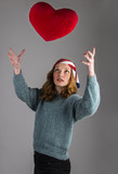 Pretty cute young girl throwing red heart shape pillow in studio. Valentines day love.