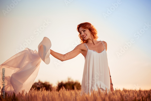 Beautiful lady in wheat field at sunset.