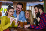 Friends in Pub drinking Beer and Looking at Smartphone - 191844071