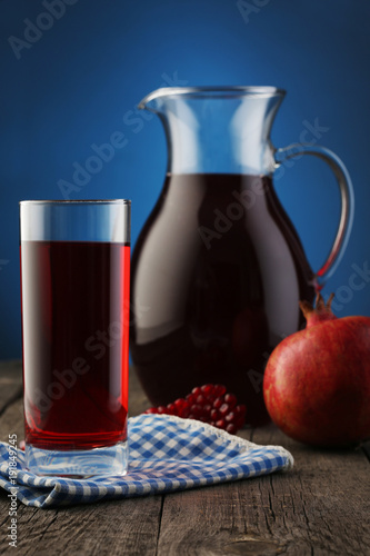 Keuken foto achterwand Sap Glass and jar of pomegranate juice with fruit on blue