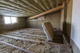 House attic under construction. Mansard walls and ceiling insulation with rock wool. Fiberglass insulation material in wooden frame for cold barrier - 191852648
