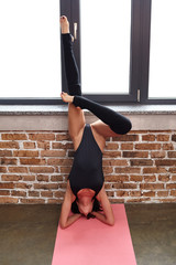 Fitness sporty woman practicing yoga, doing training in a sexy black swimsuit