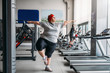 Fat woman doing balance exercise in gym