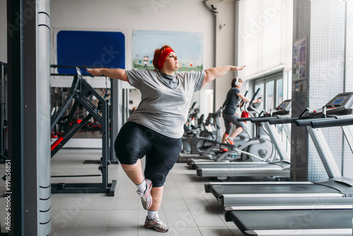 Plexiglas Fitness Fat woman doing balance exercise in gym