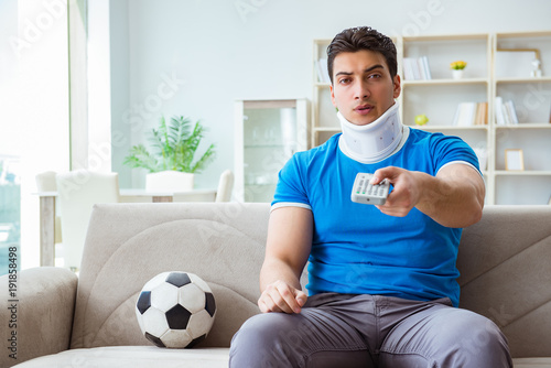 Fotobehang Voetbal Man with neck injury watching football soccer at home
