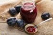 Plum jam in jar with spoon on grey wooden table
