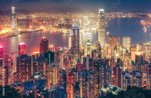 Leinwanddruck Bild Scenic view over Hong Kong island, China, by night. Multicolored nighttime skyline with illuminated skyscrapers seen from Victoria Peak