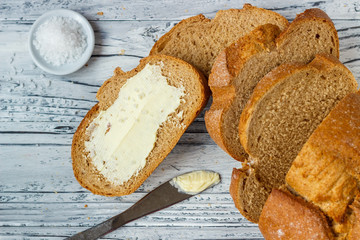 A slice of rye bread with butter on a wooden background is a close-up.