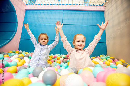 Adorable little girls with raised hands having fun in playground with pile of colorful balloons at leisure