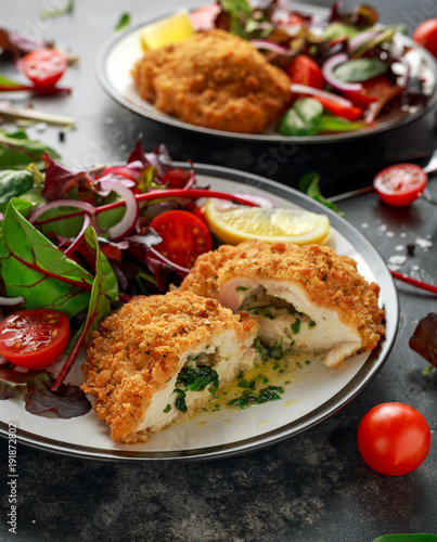 Fotobehang Kiev Breaded Chicken Kiev breast stuffed with butter, garlic and herbs served with vegetables in a plate.
