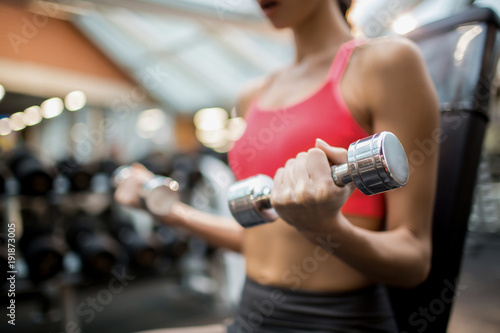 Midsection of sporty girl with dumbbells exercising in fitness club - 191873005
