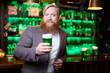 Bearded man with glass of green foaming drink looking at camera in bar on Saint Patrick day