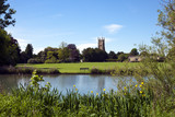 Tower of the landmark Abbey Church seen across Abbey Grounds in spring sunshine, Cirencester, The Cotswolds, Gloucestershire, UK - 191881034