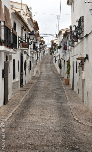 Foto op Canvas Smal steegje One of the streets of the beautiful old town Altea, located in the Costa Blanca of Spain. White houses with flowers