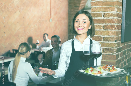 happy woman waiter demonstrating restaurant to visitors