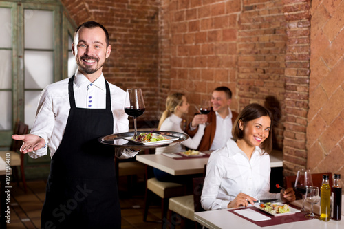 Waiter showing country restaurant to visitors