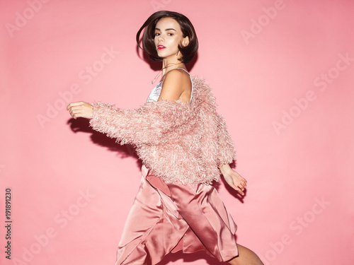 Plagát young fashion woman in pink clothes run on pink background
