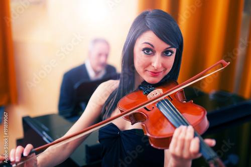 Fotobehang Muziek Portrait of a smiling woman playing her violin
