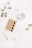 Home office desk with craft diary, pen, headphones and eucalyptus branches on white background. Flat lay, top view. - 191900004