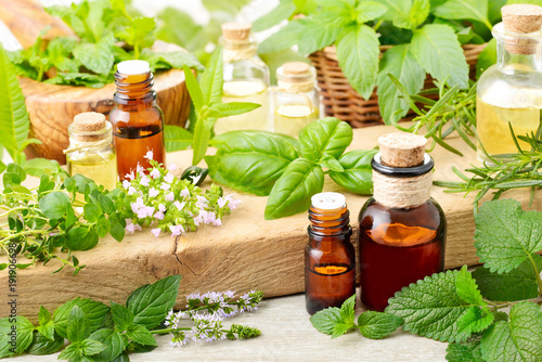 fresh herbs and essential oil on the wooden table