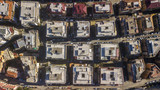 Perpendicular aerial view of a group of buildings in the Tuscolana district in Rome, Italy. All the roofs are walkable and full of antennas and TV dishes. down the streets lit by the sun. - 191907024