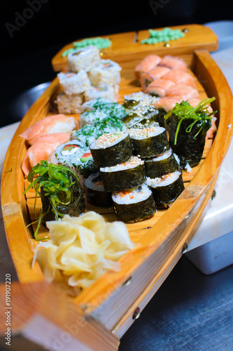 Keuken foto achterwand Sushi bar many kinds of sushi on a wooden stand in the form of a ship