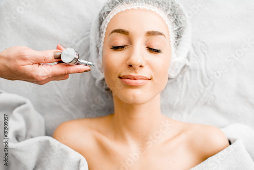 Young woman during the professional hydration procedure on the face in the cosmetological office